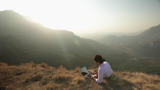 vídeos y material grabado en eventos de stock de businessman working on a laptop on the cliff of mountain  - en el borde