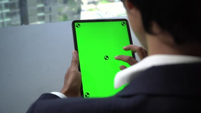vídeos de stock, filmes e b-roll de homem de negócios que trabalha em um portátil com tela verde - placa