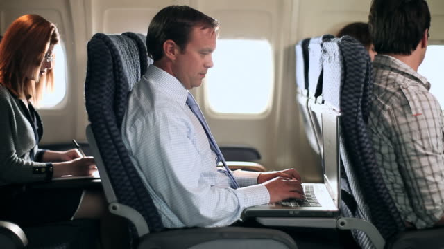 vídeos y material grabado en eventos de stock de businessman working on aeroplane - asiento de vehículo
