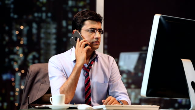 vídeos de stock e filmes b-roll de ms businessman working on computer and using phone in office - camisa e gravata