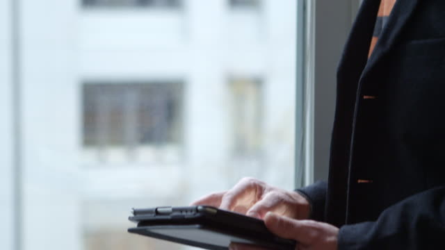 CU TU Businessman working on digital tablet and looking out window in office