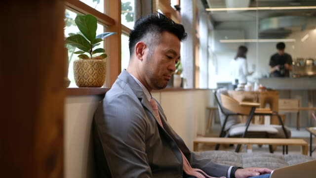 businessman working on his laptop at a cafe - only japanese stock videos & royalty-free footage