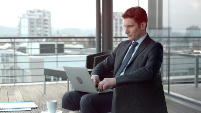 Businessman working on his laptop in a terrace lounge overlooking the city