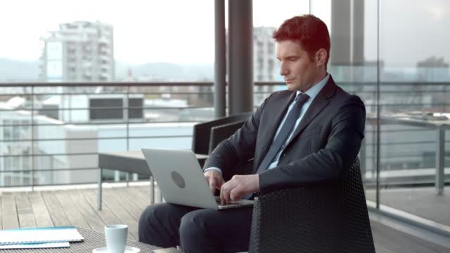 ビジネスマンの街を見下ろすテラス ラウンジで彼のラップトップに取り組んで - 座る点の映像素材/bロール