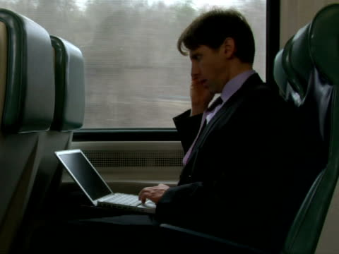 ms, businessman working on laptop and talking on mobile phone in train, chappaqua, new york state, usa - anno 2007 video stock e b–roll