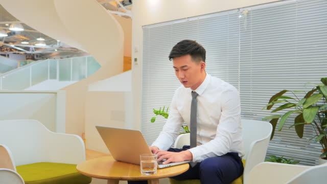 vídeos de stock e filmes b-roll de ms businessman working on laptop in office - camisa e gravata