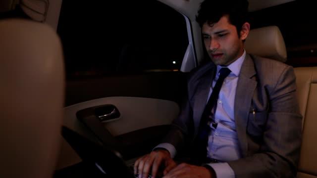 businessman working on laptop in the car, delhi, india - beifahrersitz oder rücksitz stock-videos und b-roll-filmmaterial