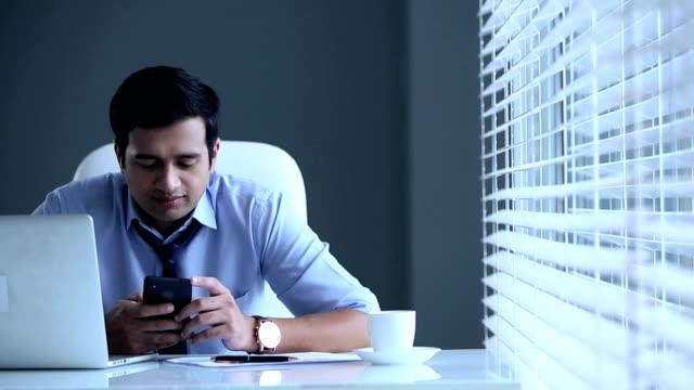 Businessman working on mobile phone, Delhi, India