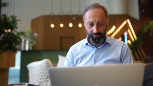 vidéos et rushes de homme d'affaires travaillant sur l'ordinateur portatif de bureau - main au menton