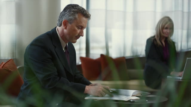 MS Businessman working on paperwork in lobby / Bellevue, Washington, USA
