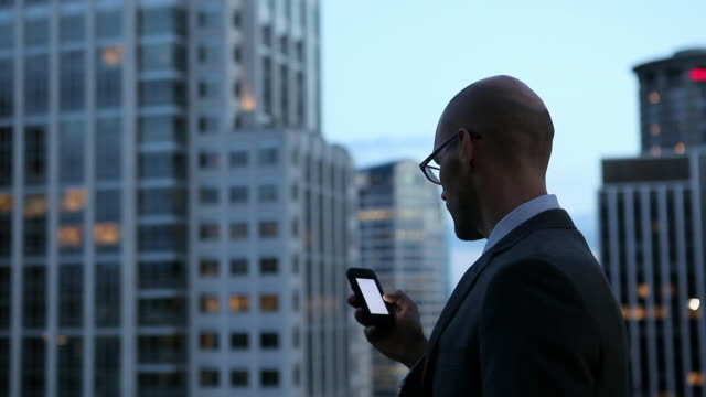 MS Businessman working on smart phone standing on deck looking out over cityscape at night/Seattle, Washington, USA