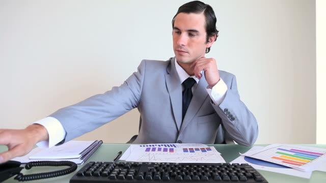 businessman working while picking up the phone - solo un uomo di età media video stock e b–roll