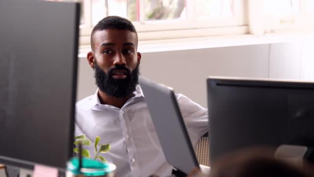 vidéos et rushes de ms businessman working with colleagues at workstation in high tech start up office - s'impliquer à fond