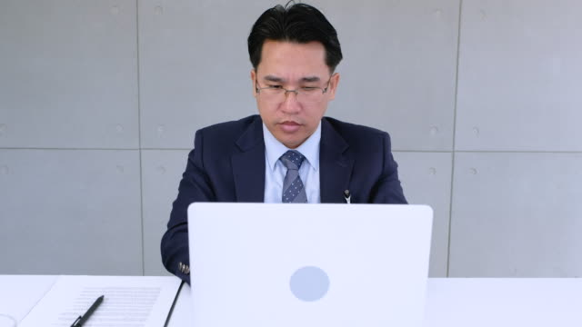 Businessman working with laptop and paperwork in modern office