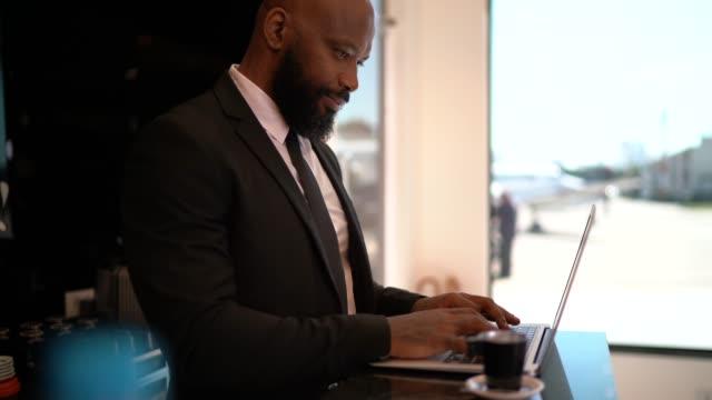 vídeos de stock, filmes e b-roll de homem de negócios que trabalha com portátil em uma sala vip do aeroporto - área de embarque de aeroporto