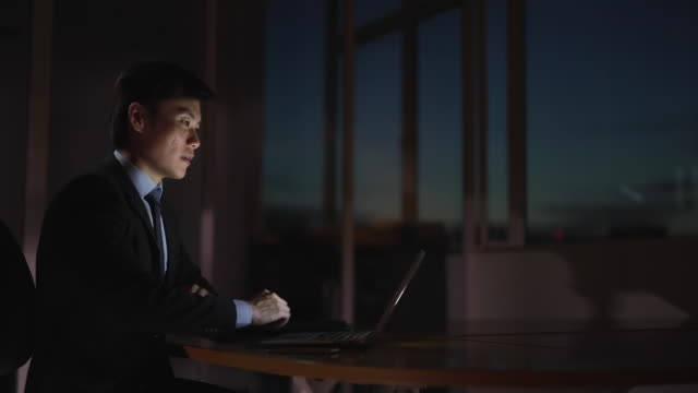 ms selective focus businessman works on his lap top late at night / singapore - working overtime stock videos & royalty-free footage