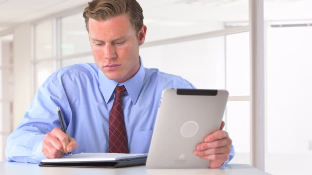 businessman writing notes and researching on tablet