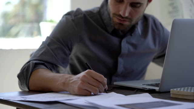 businessman writing on documents by laptop at desk - schreiben stock-videos und b-roll-filmmaterial