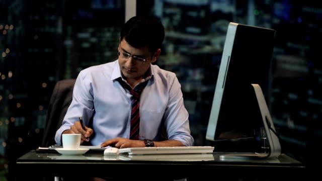 vídeos de stock e filmes b-roll de ms businessman writing on notepad and using computer in office - camisa e gravata