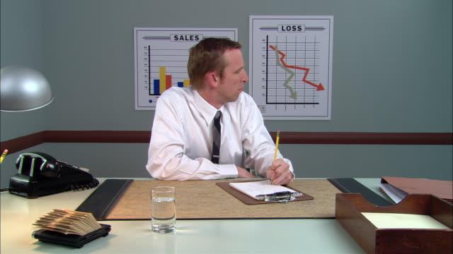 vídeos y material grabado en eventos de stock de ms businessman writing on pad at desk/ man looking over shoulder at graph indicating loss and looking worried/ new york city - camisa y corbata