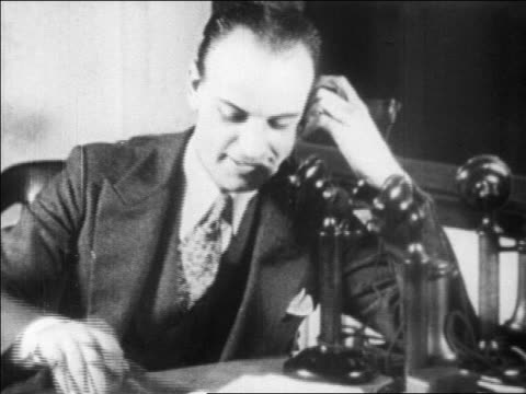 b/w 1929 businessman writing while talking on telephone in office / newsreel - einzelner mann über 30 stock-videos und b-roll-filmmaterial