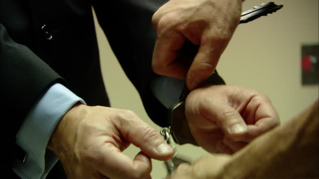 vídeos de stock, filmes e b-roll de cu businessman's hands being handcuffed by police officer/ new jersey - algema