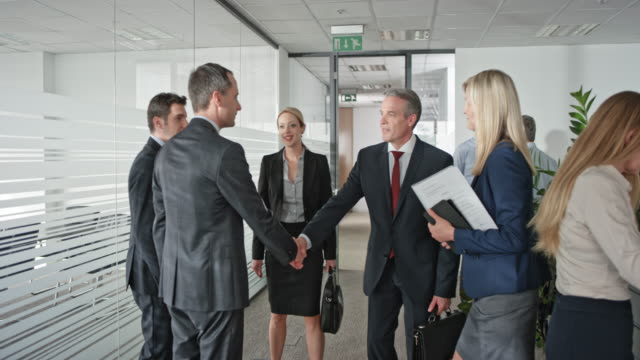 businessmen and a businesswoman shaking hands before entering the meeting room with a female assistant - entering stock videos & royalty-free footage