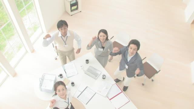 businessmen and businesswomen jumping up raising right hands - 4人点の映像素材/bロール