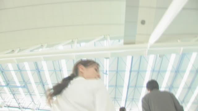 businessmen and businesswomen on escalators - 4人点の映像素材/bロール