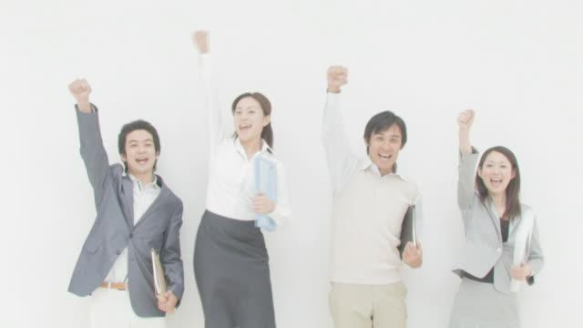 Businessmen and businesswomen raising right hands smiling