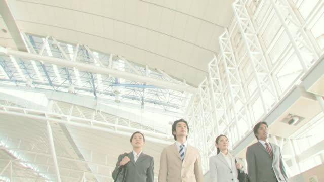 businessmen and businesswomen walking side by side - 4人点の映像素材/bロール