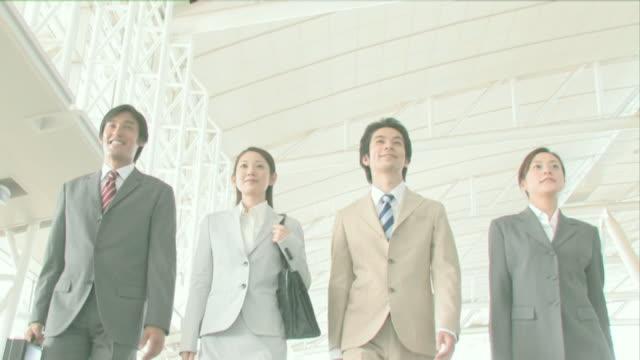 businessmen and businesswomen walking side by side - 出張点の映像素材/bロール