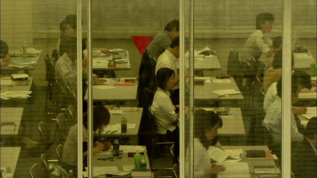 businessmen and businesswomen work at desks inside an office, japan. available in hd. - 勉強する点の映像素材/bロール