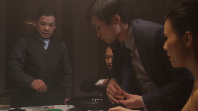 Businessmen and female playing roulette in Casino