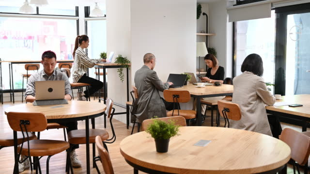 businessmen and woman working in open plan office coworking space - coworking stock videos & royalty-free footage