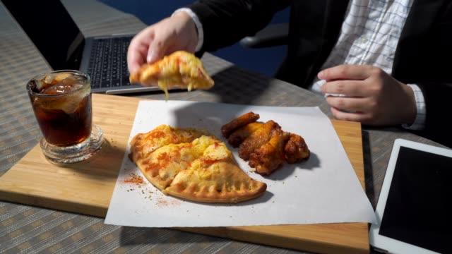 ビジネスマンは机の上でピザとバーベキューチキンレッグを食べています。4k 解像度。 - unhealthy eating点の映像素材/bロール