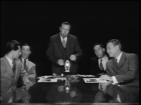 b/w 1953 businessmen at conference table watching upside down film / man adjusts film + smokes cigar - sigaro video stock e b–roll