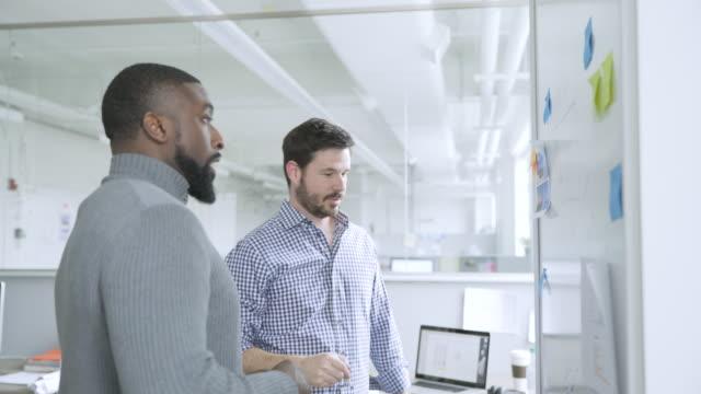 businessmen brainstorming at wall in startup office - vanguardians stock videos & royalty-free footage