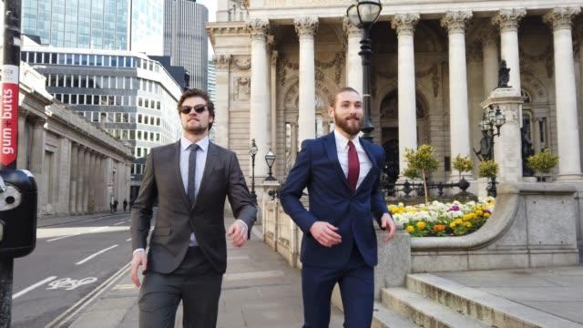vidéos et rushes de collègues d'hommes d'affaires sur l'aller dans la ville-centre de londres - tenue habillée