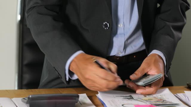 stockvideo's en b-roll-footage met zakenlieden tellen geld en plan financiën voor projecten en gebruik rekenmachines voor analyseproject documenten en grafiek financieel diagram werken op de achtergrond op kantoor tafel - graph