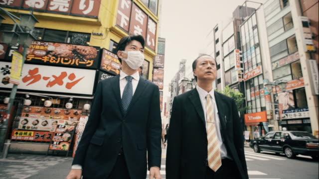 businessmen crossing street - kirurgmask bildbanksvideor och videomaterial från bakom kulisserna