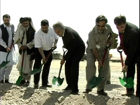 businessmen digging dirt with shovels during ground breaking ceremony / afghanistan - 背広点の映像素材/bロール