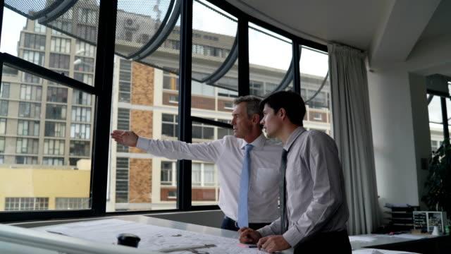 vídeos de stock, filmes e b-roll de businessmen discussing over blueprint by window - camisa e gravata