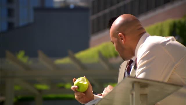 businessmen eating apples while on break outside - skjorta och slips bildbanksvideor och videomaterial från bakom kulisserna