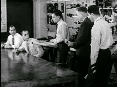 B/W 1944 3 businessmen entering meeting + showing blueprints to other men / industrial