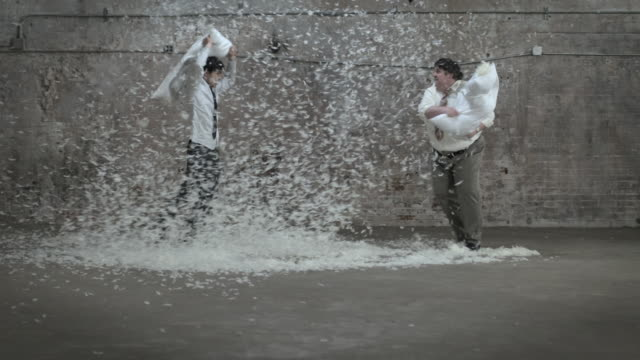 vidéos et rushes de businessmen fighting with feather pillows - oreiller