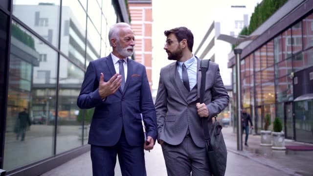 businessmen have a conversation on the way to work - side by side stock videos & royalty-free footage