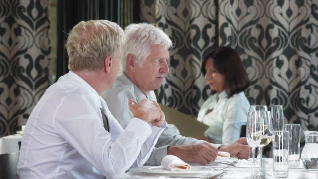 vidéos et rushes de hd dolly: hommes d'affaires ayant une conversation dans un restaurant - chemise et cravate