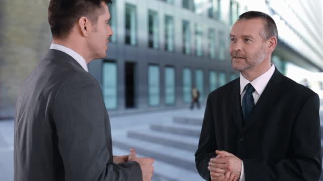 stockvideo's en b-roll-footage met businessmen having conversation - compleet pak