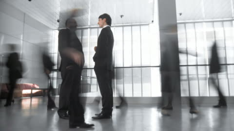 hd time-lapse: businessmen having discussion in busy corridor - fast motion stock videos & royalty-free footage